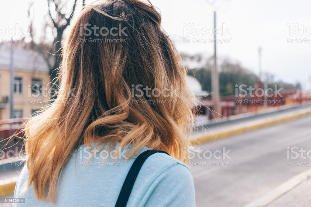 Close-up hurrying girl with disheveled wavy hair stock photo