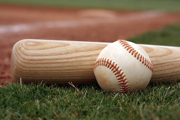 close-up if baseball and bat resting on the field - baseball bat stock photos and pictures