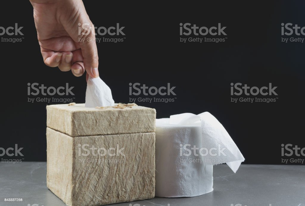 Close-up image hand pull the toilet papers roll in box with toilet papers roll on the table with dark background. stock photo