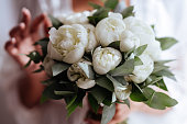 Close-up image of a beautiful and stylish wedding bouquet of white and pink peonies. Summer floral composition.