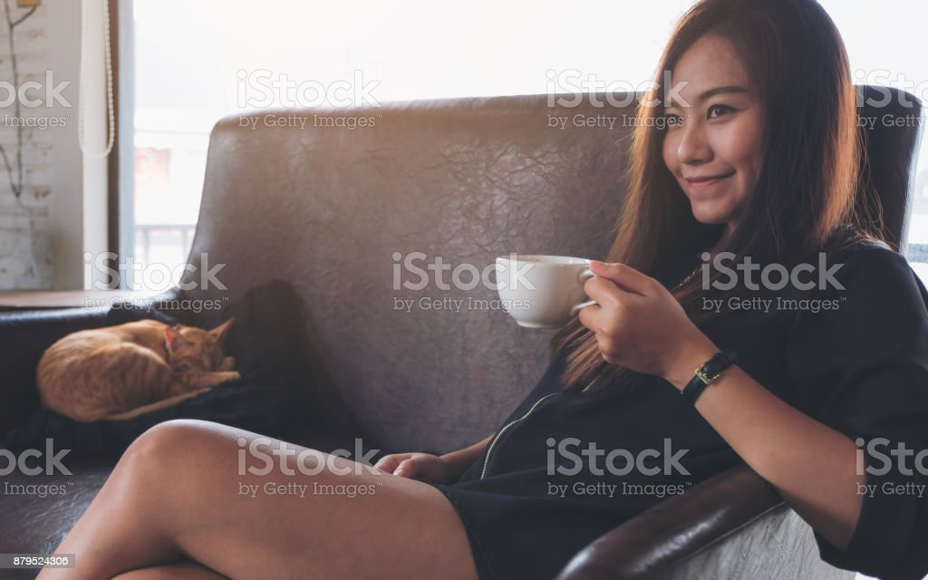 Closeup image of a beautiful Asian woman sitting on sofa while a little brown cat is sleeping on a black pillow stock photo