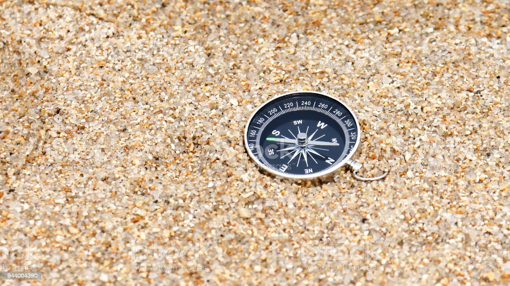 Close-up image of a compass on the sand. stock photo
