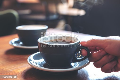 istock Closeup image of a hand holding a blue cup of hot coffee with smoke on wooden table in cafe 1030155158