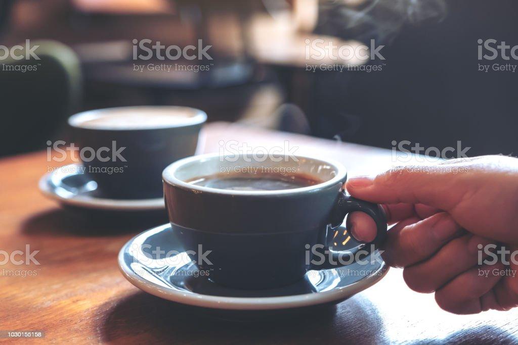 Image gros plan d'une main tenant une tasse bleue de café chaud avec de la fumée sur une table en bois dans le café - Photo