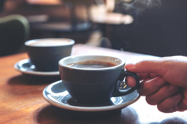 closeup image of a hand holding a blue cup of hot coffee with smoke on wooden table in cafe - coffee stock pictures, royalty-free photos & images