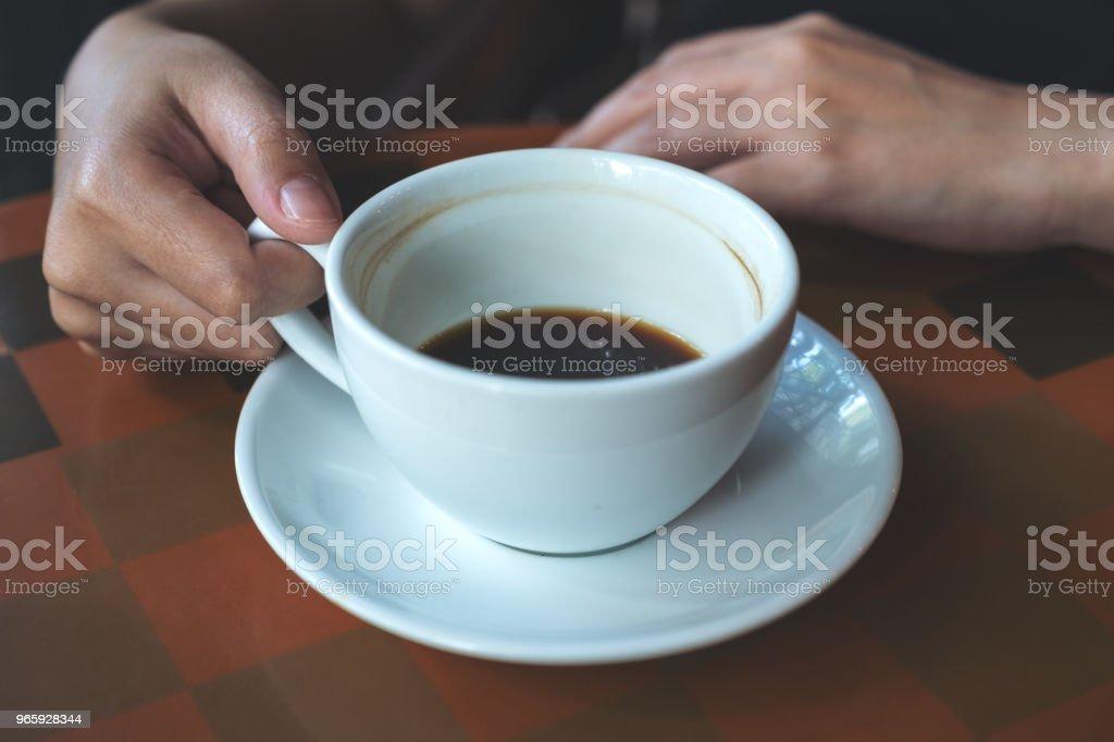 Close-up beeld van een hand houden en warme koffie drinken in café - Royalty-free Alleen volwassenen Stockfoto