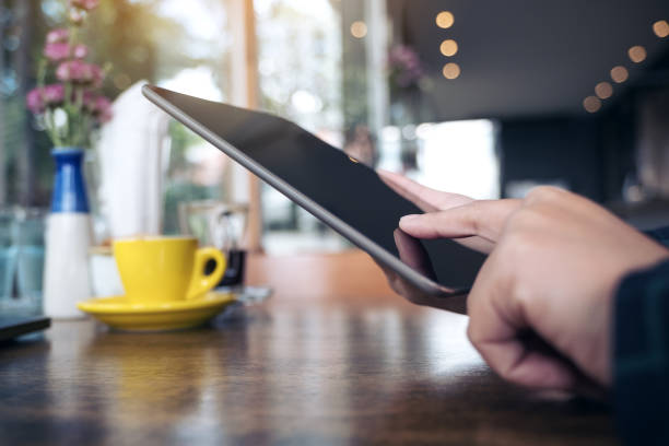 closeup image of a hand pointing , touching and using tablet pc with blur background in cafe - apply online stock photos and pictures