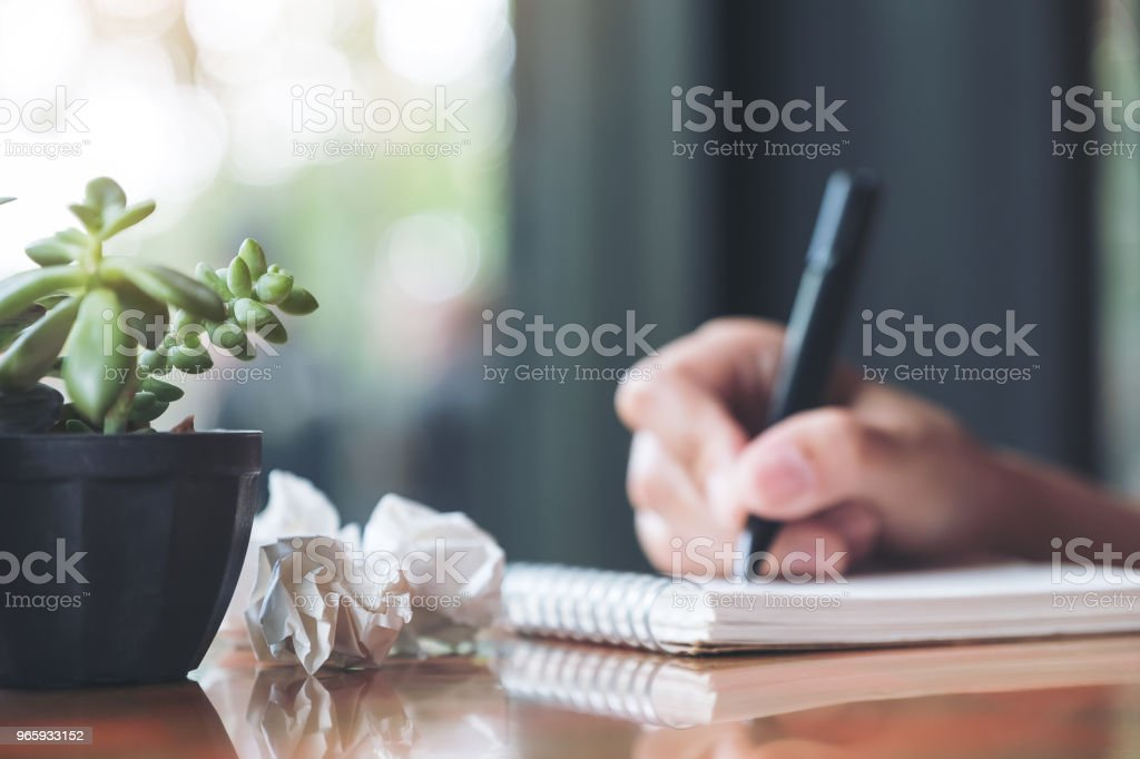 Closeup image of a hand working and writing down on a white blank notebook with screwed up papers on table - Royalty-free Adult Stock Photo