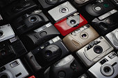 Close-up image of a large group of analog vintage 35mm film cameras lying in arrangement close to each other
