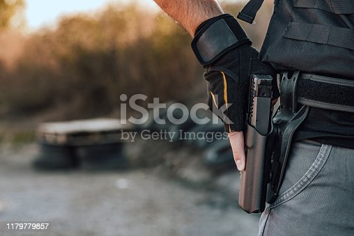 Close-up image of a man holding hand gun in holster on the belt.