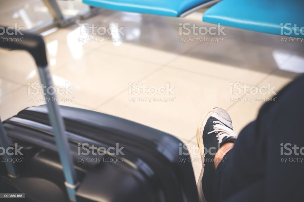 Closeup image of a man sitting and waiting for depart from airport with black baggage stock photo
