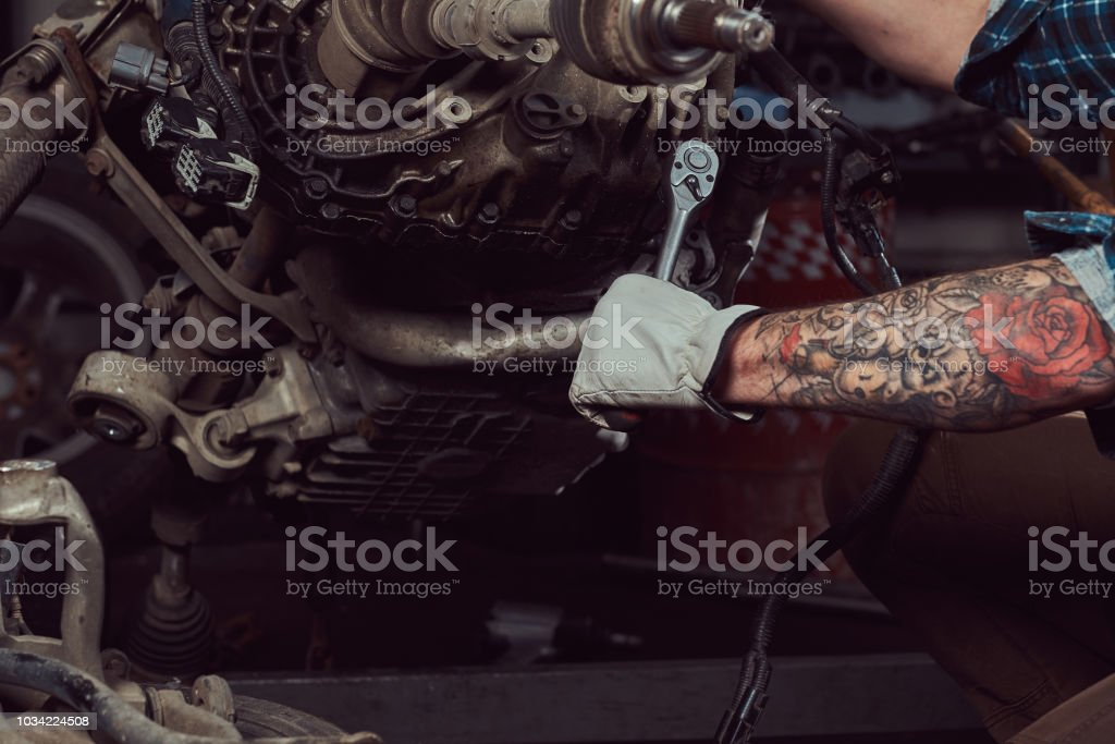 Close-up image of a tattooed mechanic specialist repairs the car engine with a wrench in the garage. stock photo