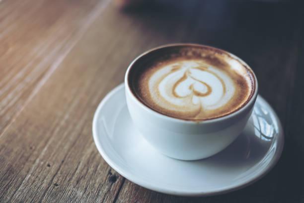 nahaufnahme bild einer weißen tasse heißen latte kaffee auf vintage holztisch im café - mocca stock-fotos und bilder
