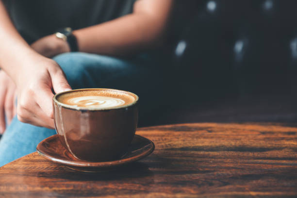 Closeup image of a woman holding  a cup coffee on vintage wooden table in cafe stock photo
