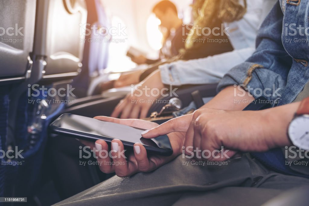 Closeup image of a woman holding and touching at a black smart phone...