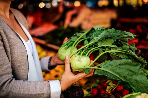 Close-up image of a woman holding kohlrabi at market. Close-up image of a woman holding kohlrabi at market. brassica rapa stock pictures, royalty-free photos & images