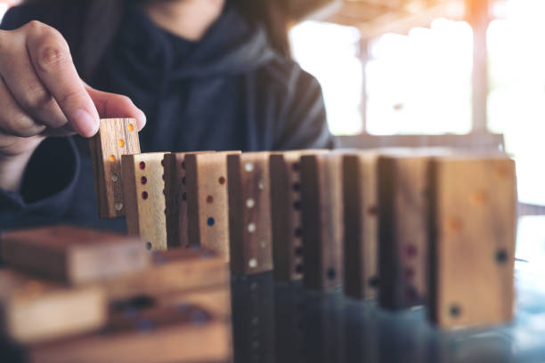 Closeup image of a woman putting wooden domino game in order on table stock photo