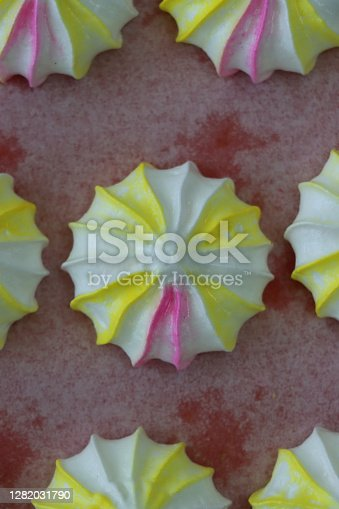 Stock photo showing elevated view of greaseproof baking parchment containing rows of multi-coloured, piped cooked meringue peaks. The freshly piped circus meringue kisses are coloured with pink and yellow food colouring.
