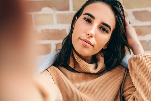 Close-up image of beautiful young blonde woman smiling, wearing beige sweater, making self portrait against birck wall. Attractive brunette female taking selfie. People, travel, lifestyle concept. stock photo