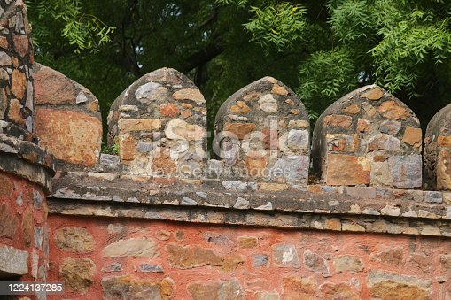 Stock photo showing crenellation detail of brick red Indian architecture.