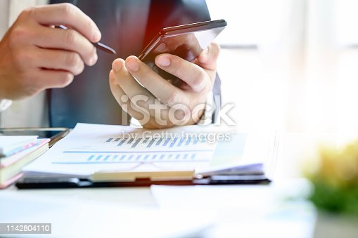 Closeup image of businessman using stylus working on mobile smartphone while sitting at office desk. Copy space.