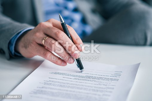 Close-up image of businessman with contract and pen in his hands.