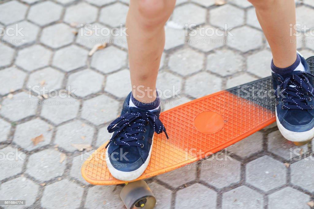 Closeup image of children's feet at skateboard. stock photo