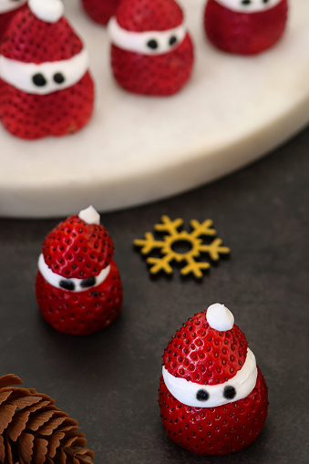 Stock photo showing close-up view of Christmas party themed food idea of strawberry and whipped cream Father Christmases. Strawberries are a popular fruit that is considered to be an especially healthy snack 'super food', since they are packed with beneficial antioxidants and fibre, being a good source of vitamin C.