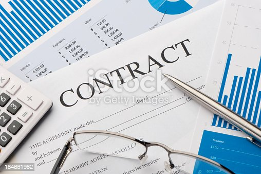 Contract form on a desk with pen, calculator and glasses