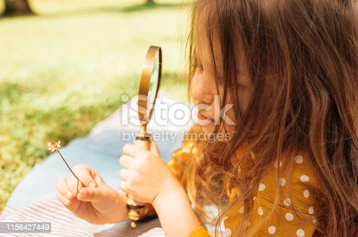 istock Closeup image of cute little girl exploring the nature with magnifying glass outdoors. Child playing in the forest with magnifying glass. Curious kid looking through magnifier to small flower in park. 1156427449