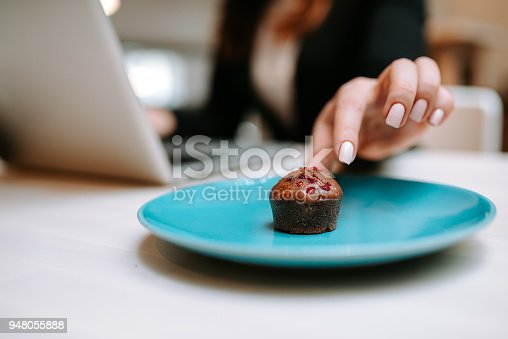 Close-up image of female hand taking delicious muffin with berries.