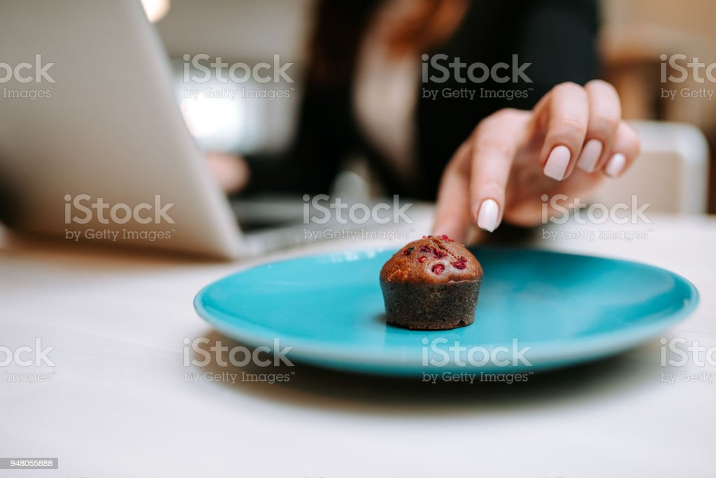 Close-up image of female hand taking delicious muffin with berries. stock photo
