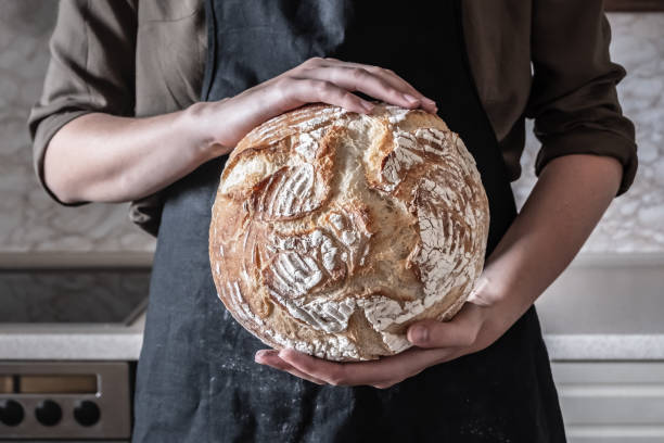 close-up image of female hands holding big loaf of white bread. - panettiere foto e immagini stock