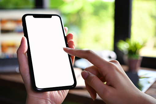 Close-up image of female hands using smartphone with blank white screen in the coffee shop