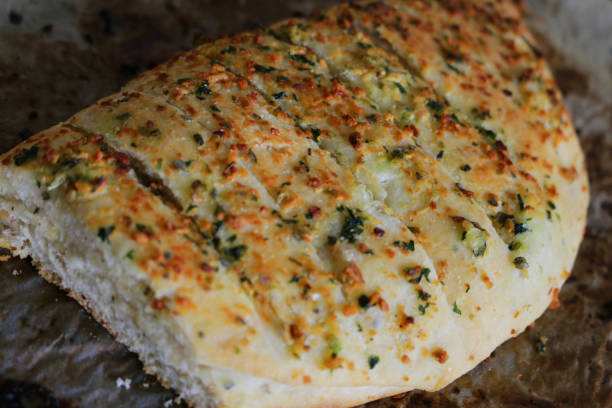 Close-up image of freshly baked, cut, artisan loaf of white, garlic bread topped with melted cheese and sprinkled with herbs on chopping board, elevated view stock photo