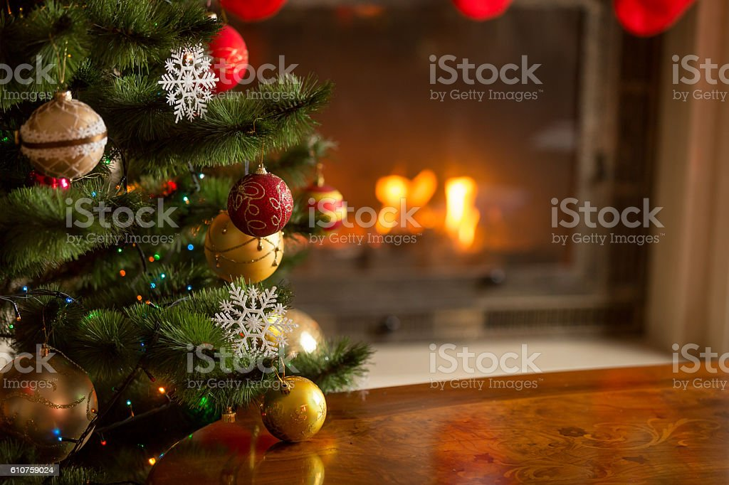 Closeup image of golden baubles on Christmas tree at fireplace stock photo