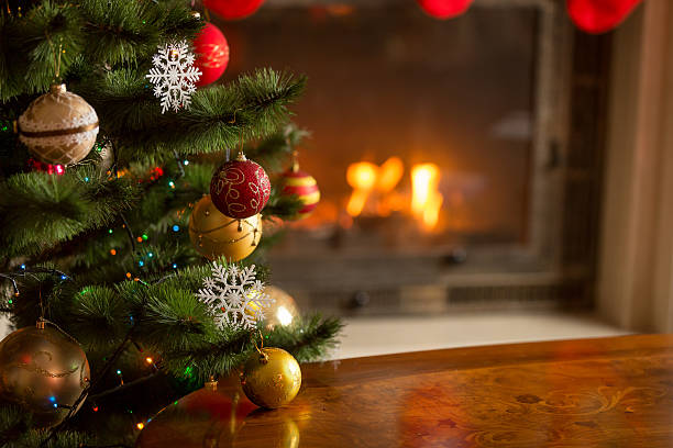 Closeup image of golden baubles on Christmas tree at fireplace Closeup image of golden and red baubles on Christmas tree in front of burning fireplace. Beautiful Christmas background christmas tree stock pictures, royalty-free photos & images