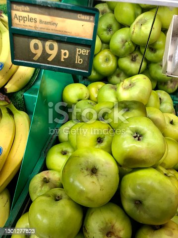 Stock photo showing a group of Bramley cooking apples and bananas being sold at an indoor fruit and vegetable market.