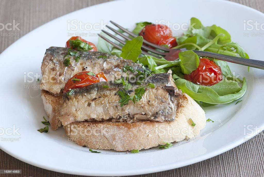 A close-up image of grilled sardines served with salad stock photo