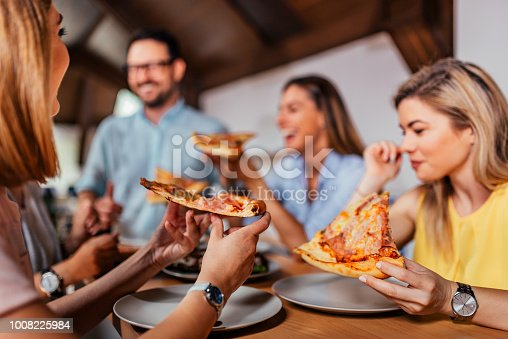 Close-up image of group of friends or colleagues eating pizza.