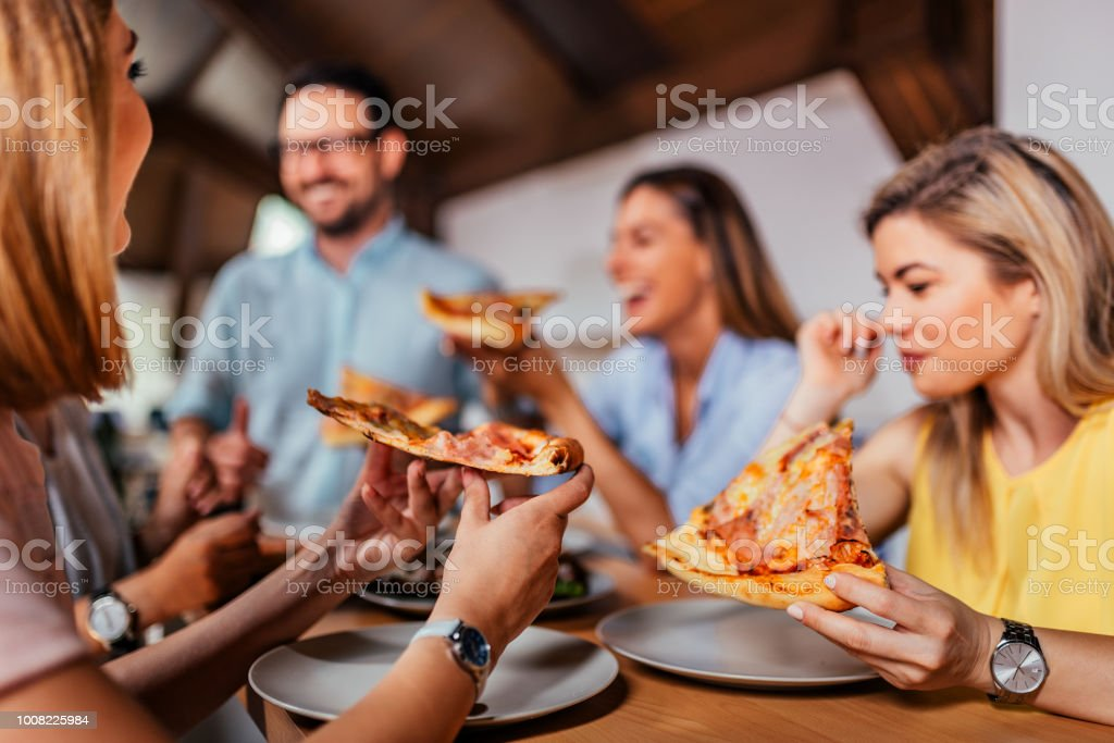 Close-up image of group of friends or colleagues eating pizza. stock photo