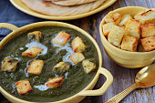 istock Close-up image of handled, yellow serving dish vegetarian meal Palak paneer (cottage cheese and spinach puree) recipe beside blue-grey cheese cloth and gold spoon, lachha paratha (flatbread), bowl cubed curd cheese, wooden background, focus on foreground 1273065408
