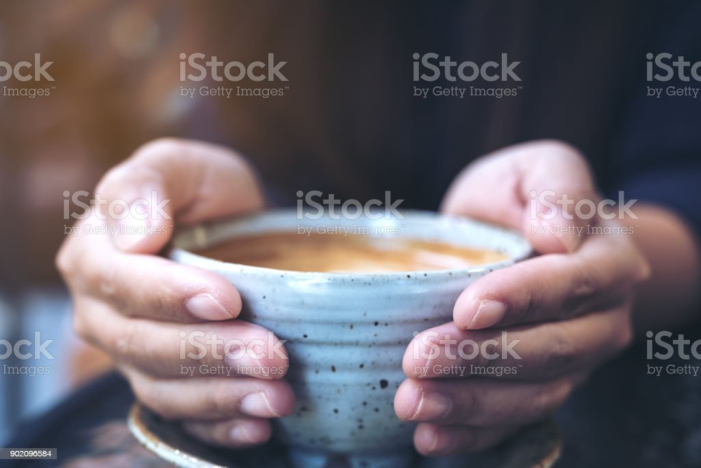 Closeup image of hands holding a cup of hot coffee on glass table in cafe stock photo