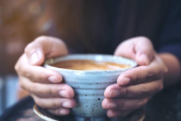 カフェのガラス テーブルでホット コーヒーのカップを置く手のクローズ アップ画像 - シンプルな暮らし ストックフォトと画像