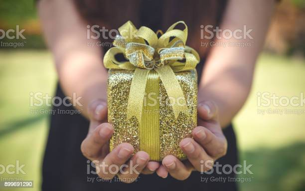 Closeup image of hands holding gold color present box with blur picture id899691290?b=1&k=6&m=899691290&s=612x612&h=7yibfbee7qtgtyhgvrj3if10cmtbqluwj3i58elui9q=