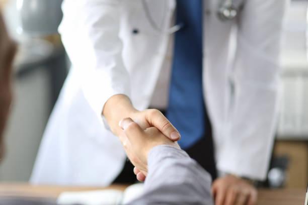 Nahaufnahme Bild von medizinischem Fachpersonal oder Arzt oder Zahnarzt Hände mit Patient schütteln. – Foto