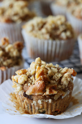 Stock photo showing close-up view of wire metal cooling rack of homemade apple muffins, with crumble topping, in paper cake cases on a marble effect surface.