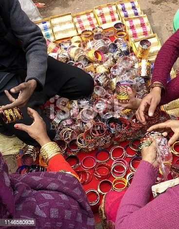 Stock photo of Indian Hindu women's hands and painted fingernails with red nail polish / varnish, selling colourful bangles and gold bracelets at street market, Connaught Place, New Delhi.