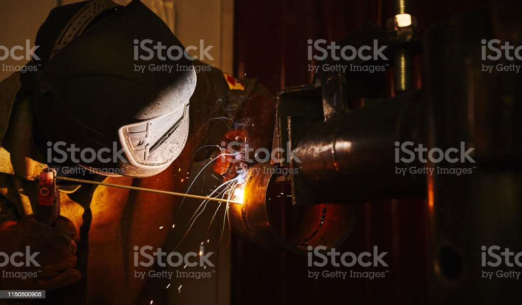 Close-up image of industrial worker at the factory welding. Industry...