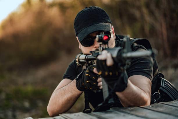Imagen de primer plano del hombre apuntando con rifle de francotirador. - foto de stock